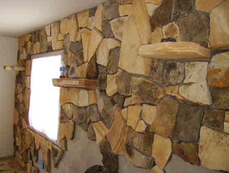 He is putting a stone veneer wall inside. Thought you may like the pictures.